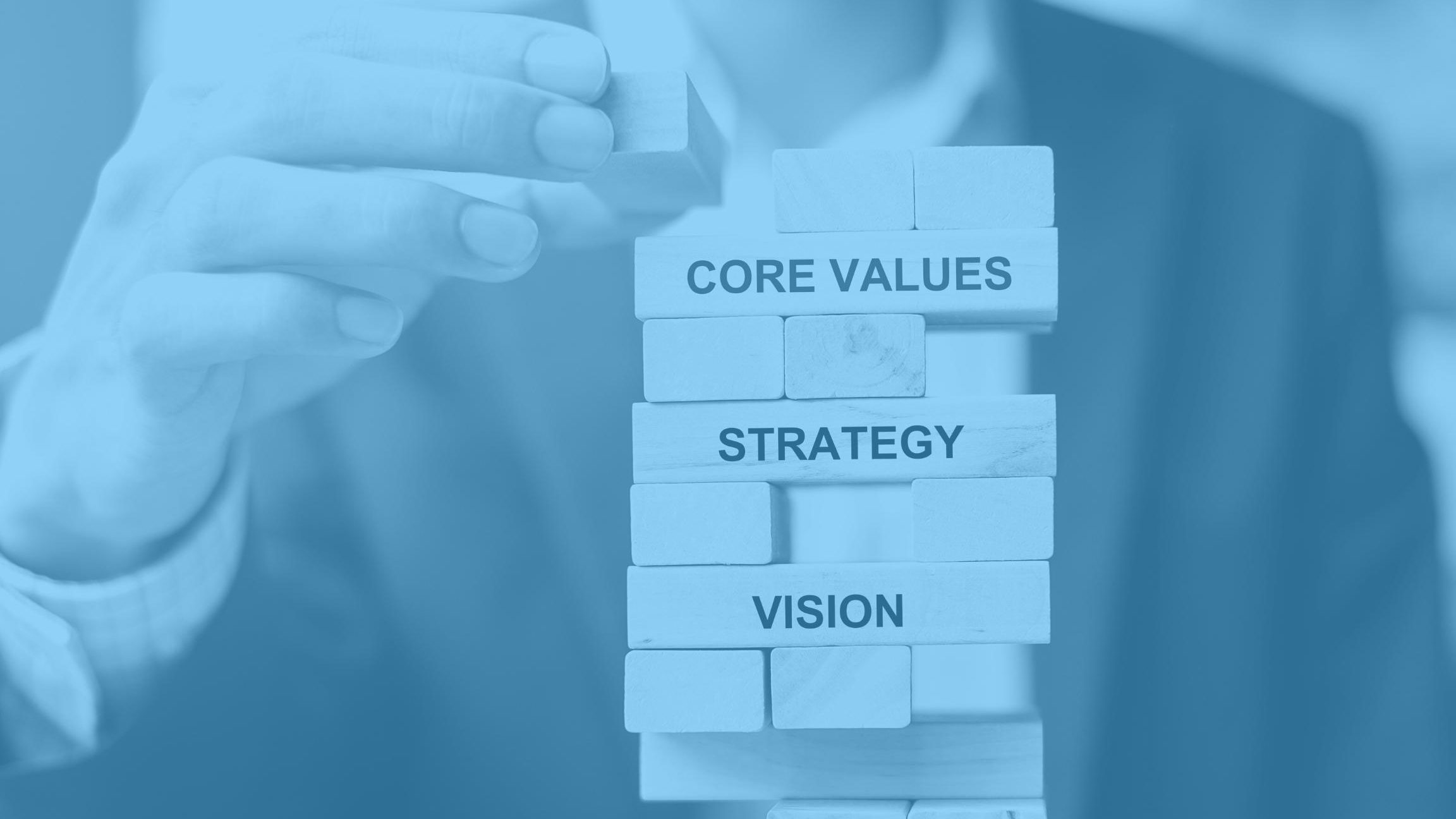 """Close up of marketing man stacking wooden blocks with the words """"core values"""", """"strategy"""", and """"vision"""" written on the sides."""
